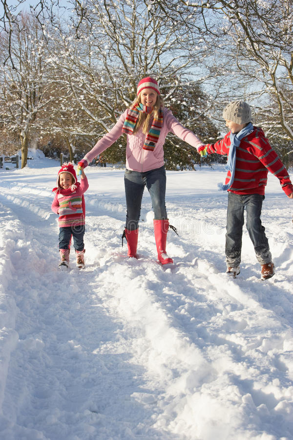 Mother Walking With Children Through Snowy Landsca stock photos