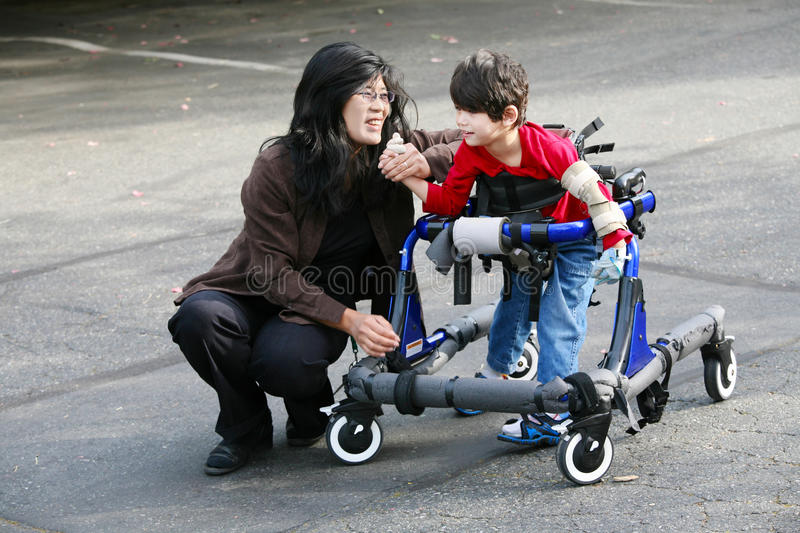 Mother walking with disabled son in walker royalty free stock photo