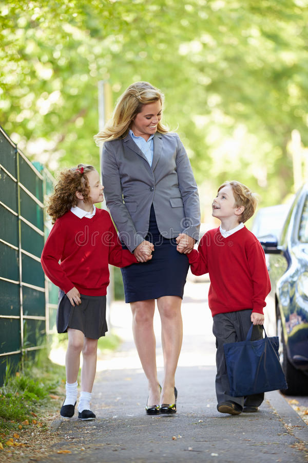 Mother Walking To School With Children On Way To Work stock images