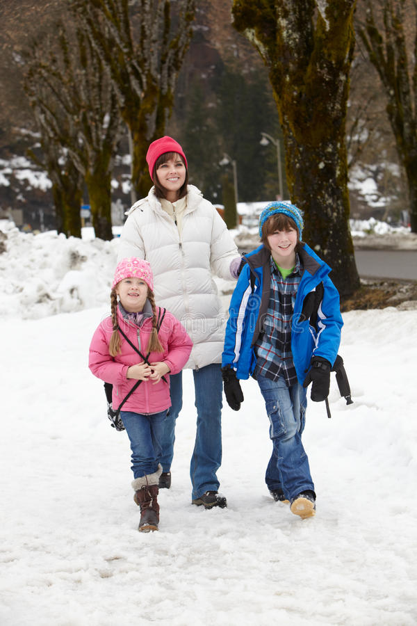 Mother Walking Two Children To School In Snow royalty free stock images