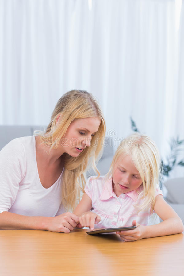 Download Mother Watching Her Daughter Using Digital Tablet Stock Photo - Image: 32233462