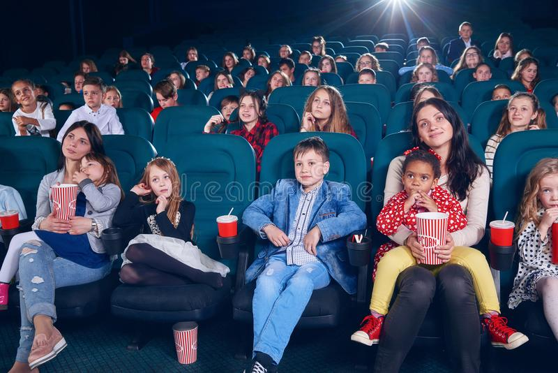 Mother watching movie with little children on first cinema row. royalty free stock images