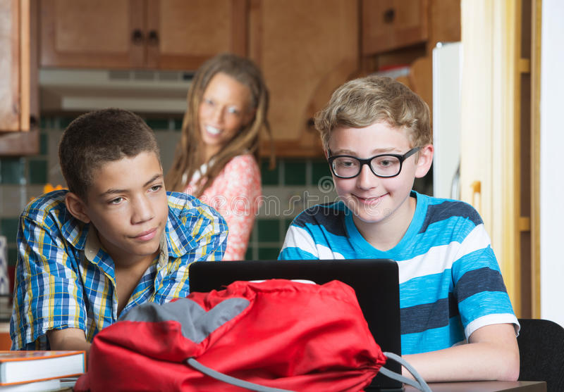Mother watching son and friend do homework stock images