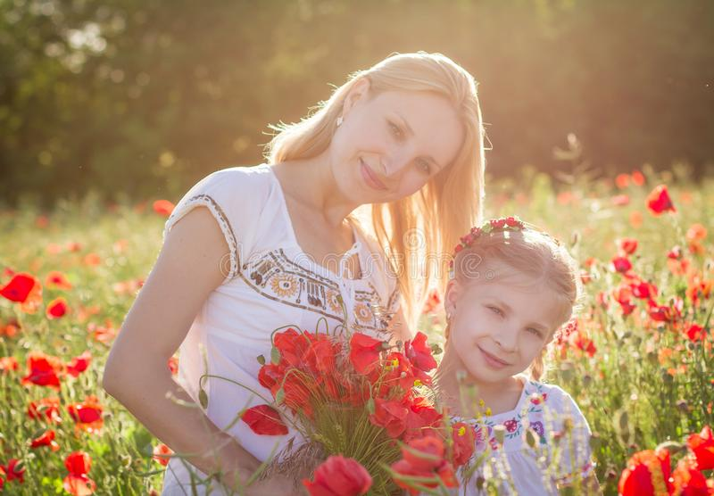 Mother in white with daughter together on blossoming red poppies field stock image