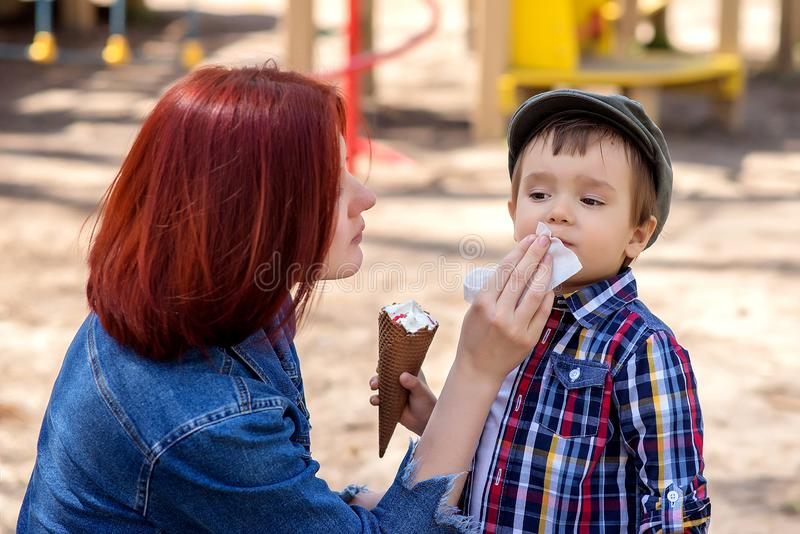 Mother wipes face of her toddler son. The boy is holding an ice-cream in waffle cone in hand. Mother care concept stock images