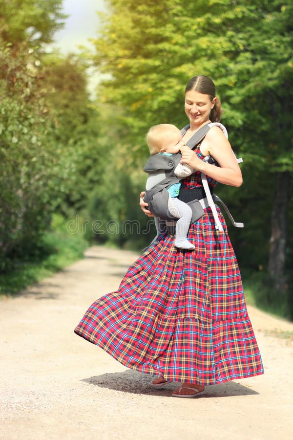 Free Mother With His Infant Son In Baby Carrier Have Fun In The Summer Park. Happy Family Moments Stock Image - 124338451