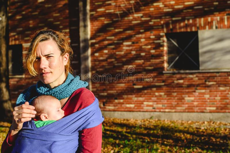 Mother woman carrying safely her newborn baby in a scarf during a walk in the sun stock photos