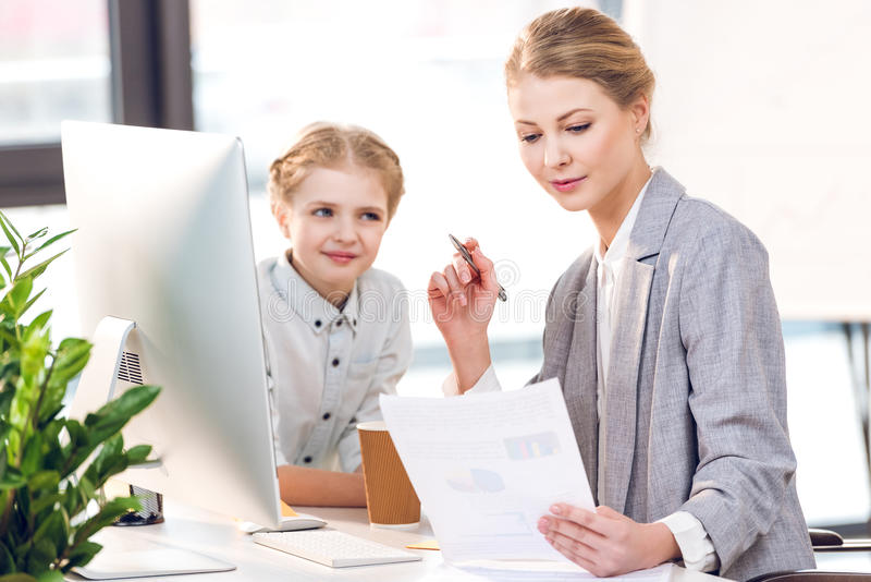 Mother working with computer and documents while daughter looking on her in business office stock images