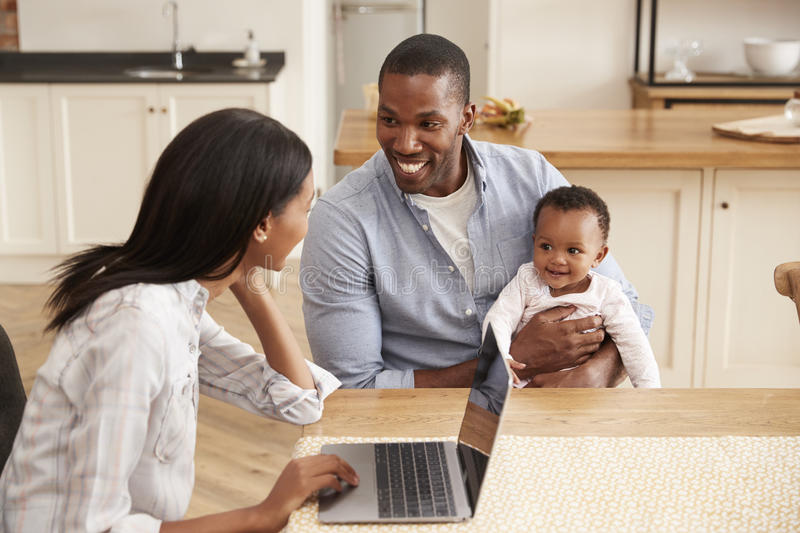 Mother Works From Home As Father Holds Baby Daughter stock images