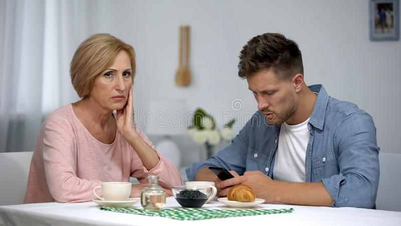 Mother worrying about adult son gadget addiction, male playing video game royalty free stock photography