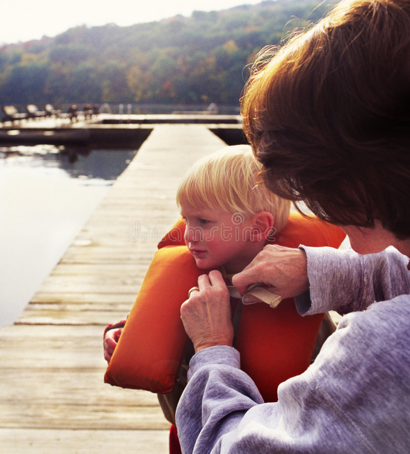 Mother and young child on dock. Mother securing life vest on child stock image