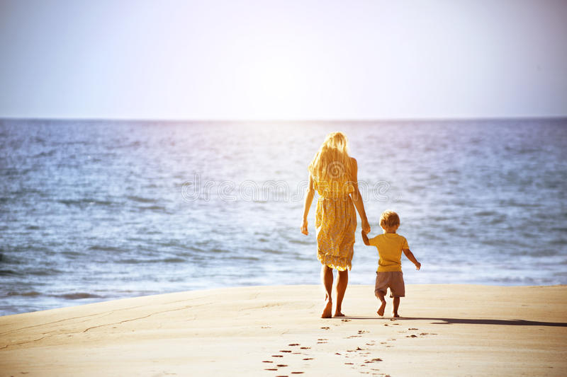 Mother and young son walk beach royalty free stock photography