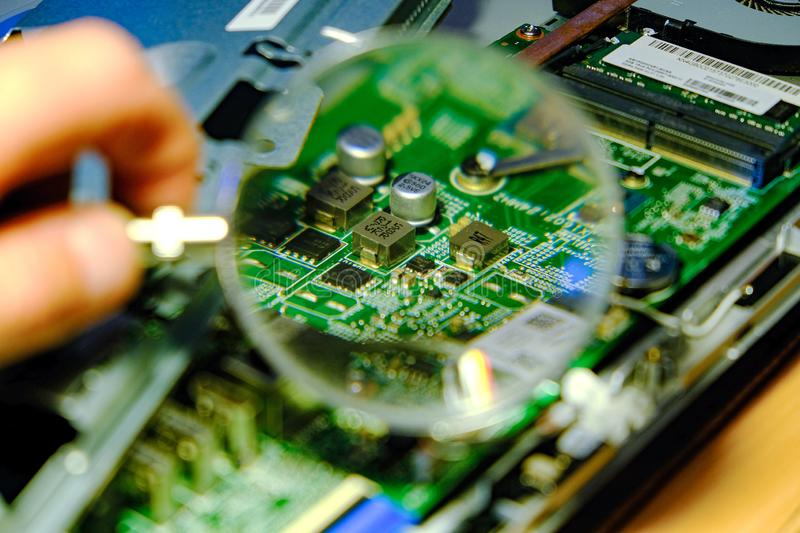 The motherboard is magnified through a magnifying glass. Hardware upgrades computer processor of the service component of the. Motherboard. The concept of royalty free stock photography