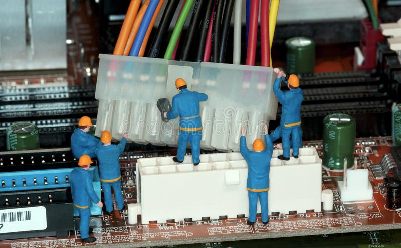 Motherboard Repair. Miniature construction worker figurines posed as if working on a computer motherboard stock photos