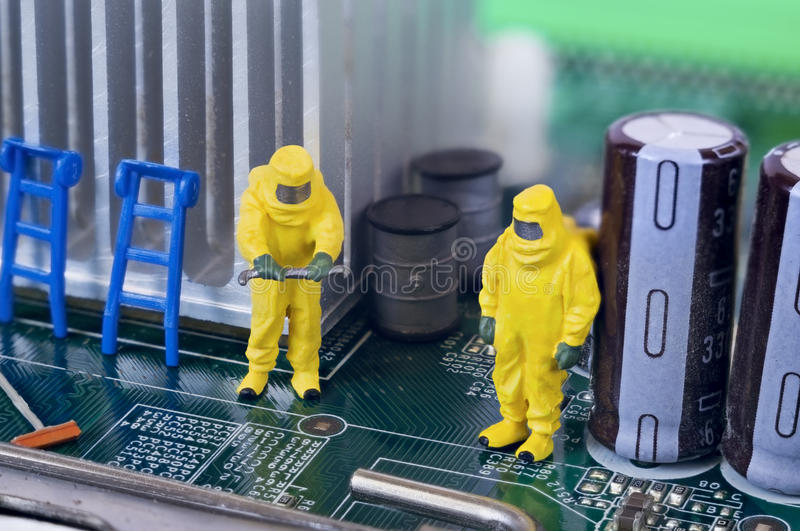 Motherboard repairing, cleaning or diagnosing concept. Two toy technicians are repairing, cleaning and diagnosing a motherboard royalty free stock photography
