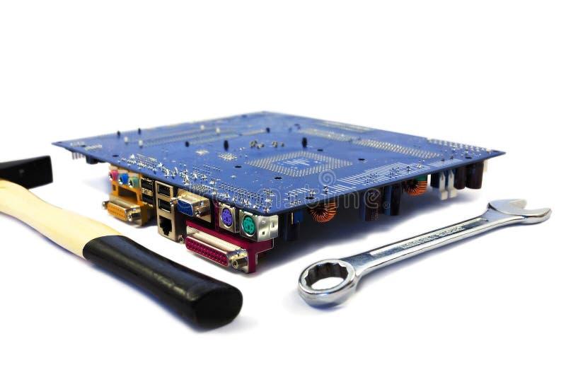 Computermotherboard met moersleutel en hamer