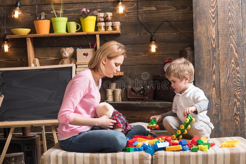 Motherhood concept. Family play with constructor at home. Mom and child play with details of constructor, plastic bricks. Nursery with chalkboard on background royalty free stock photos