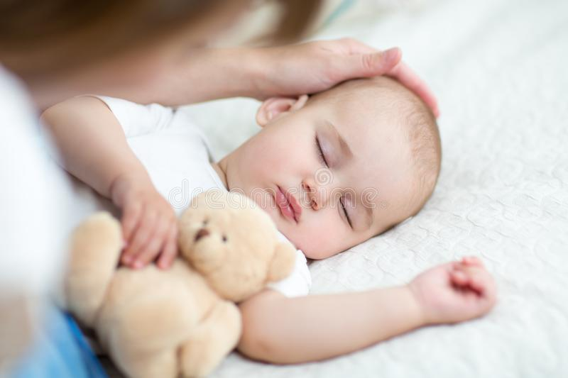 Motherhood. Parenthood. Young mother looking at her baby infant sleeping in bed stock photo