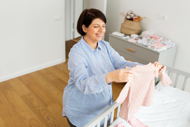 Happy pregnant woman setting baby clothes at home royalty free stock images