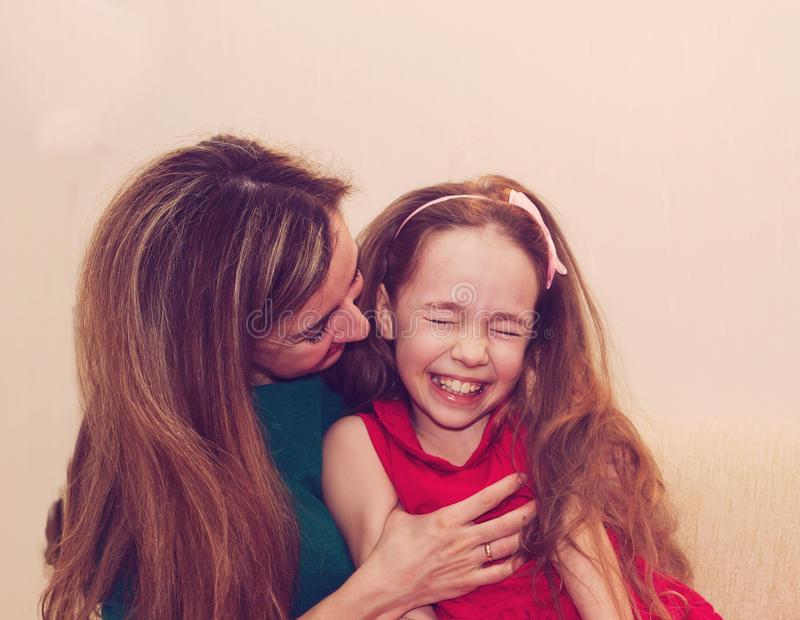 Motherhood is pure joy. Beautiful young woman hugging little girl, smiling and looking at her with love. Mother and daughter royalty free stock photos