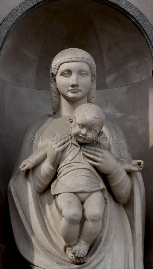Motherhood. Shot in color, detail on an sculpture representing a mother holding her son placed on the facade of this historic building, set in Eixample royalty free stock photography