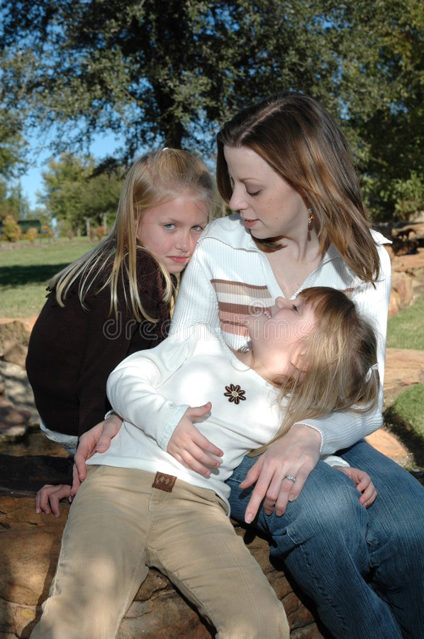 Mothers Affection. A mom sits outside in a park with her two beautiful daughters spending time with her. Family spending time together royalty free stock photos