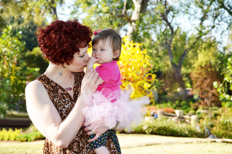 Mothers Affection. A beautiful mother and daughter in a colorful fall park. Mom is kissing babys hand in a tender show of affection royalty free stock photos