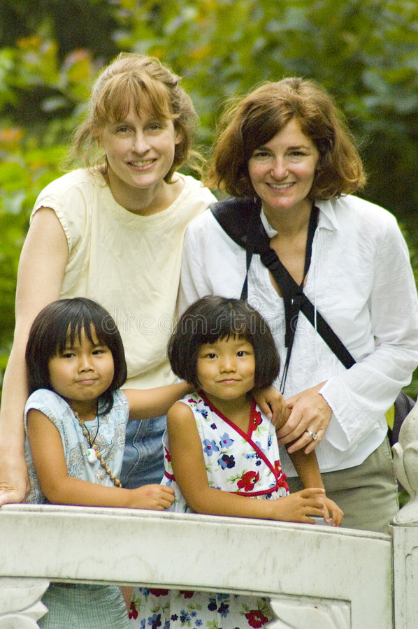 Mothers and Daughters. Two Caucasian mothers stand behind their cute young Asian daughters on a bridge before a leafy spring background, one of the daughters royalty free stock photography