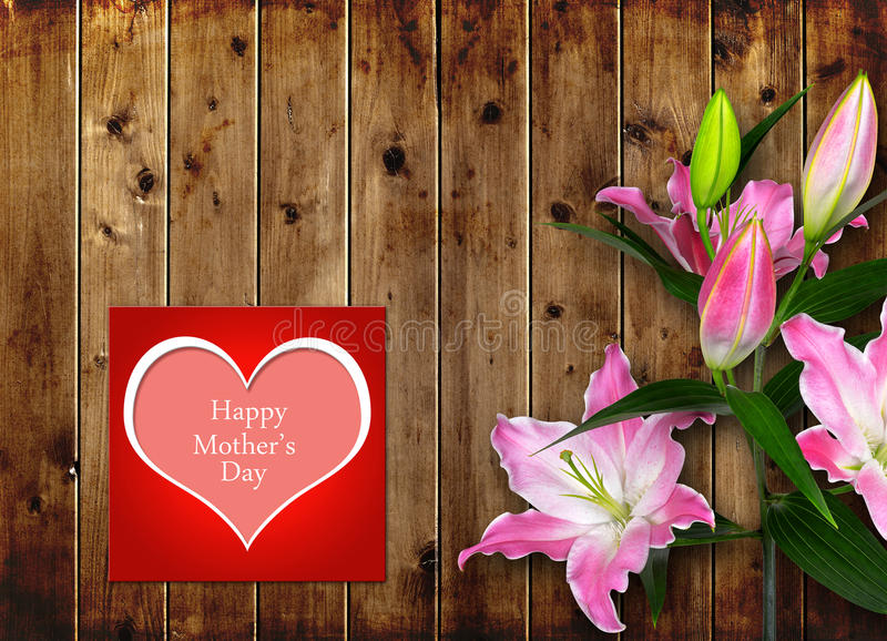 Mothers day card with pink Lily flower. On wooden board royalty free stock image