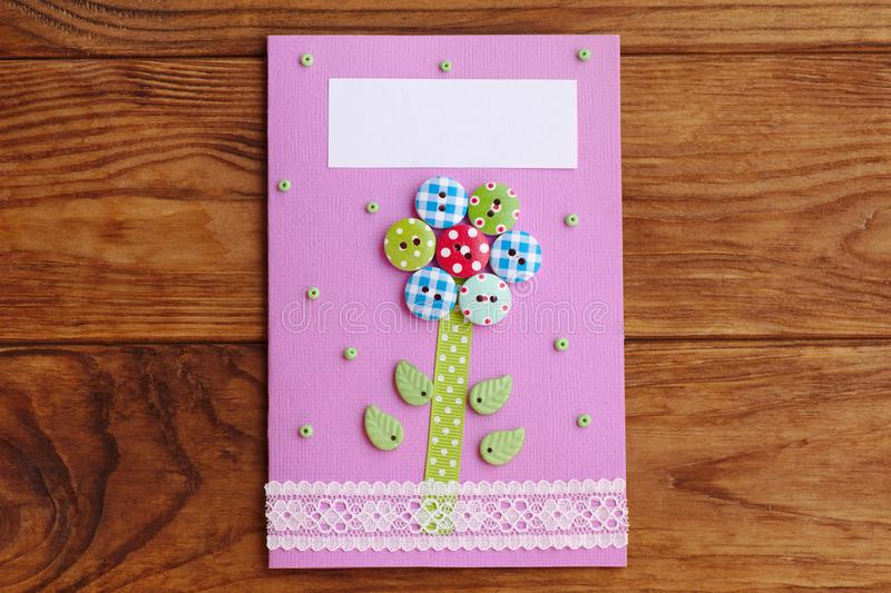 Mother`s day or Mom birthday greeting card with flower isolated on a wooden background. Easy handmade card to make in school stock photography