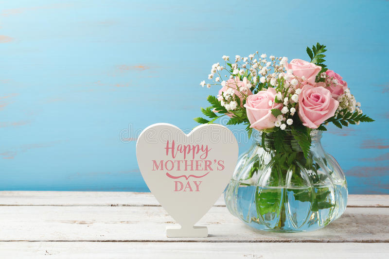 Mothers day greeting card with rose flower bouquet in glass vase and heart shape sign. Over wooden background stock image