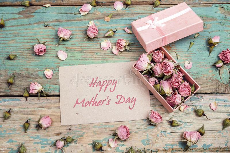 Mothers Day greeting message with little pink roses in a box on stock photo