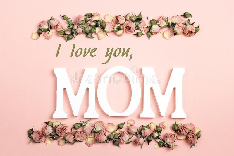 Mothers Day greeting message with small dry roses on pink background. Flat lay, top view. stock image