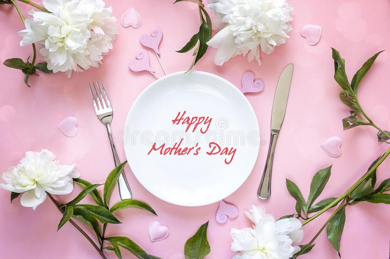 Mothers Day greeting message with table setting, white peonies a royalty free stock photo