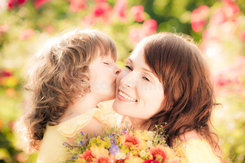 Mothers day. Happy women and child with beautiful spring flowers against green background. Family holiday concept. Mothers day