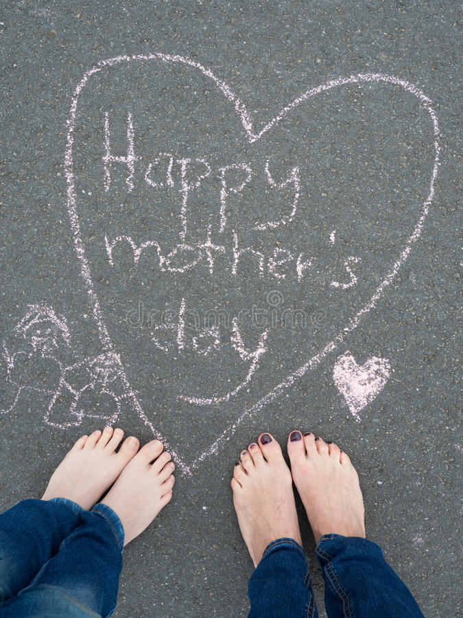 Mothers day - heart shape chalk drawing and the feet of a child. And of a woman stock photography
