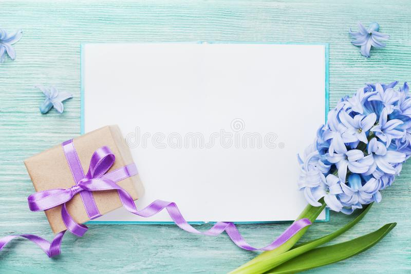 Mothers Day holiday card with empty notebook for greeting text, gift or present box and fresh flowers top view. Mothers Day holiday card with empty notebook for royalty free stock images