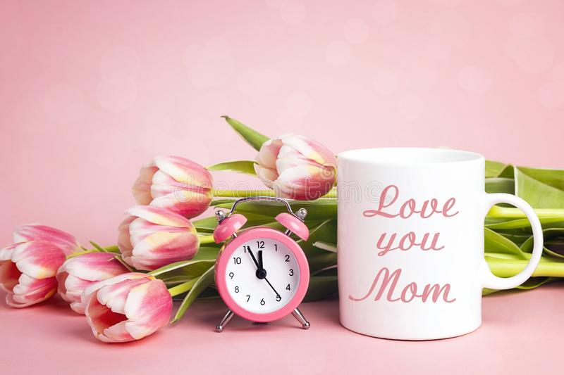 Mothers day message on white coffee mug with tulip flowers and  alarm clock on pink  background royalty free stock photos