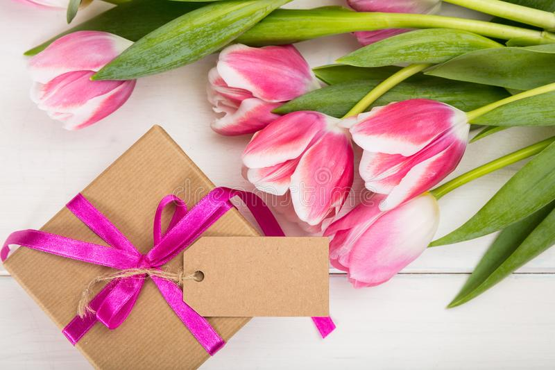 Mothers day. Pink tulips and a blank card gift on white background, top view, copy space royalty free stock photos
