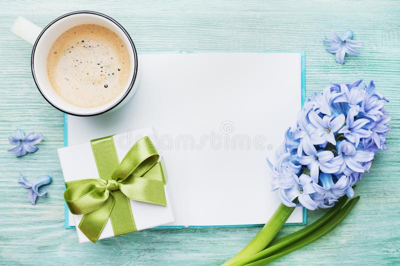 Mothers Day spring holiday card with empty notebook for greeting text with cup of coffee, gift or present box and hyacinth flowers royalty free stock photography