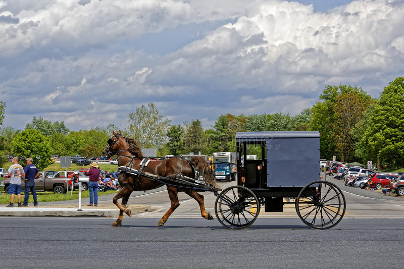 Mothers Day Truck Convoy in Lancaster Pennsylvania. LANCASTER PA - MAY 14 2017: An Amish carriage passes the Make-A-Wish Foundation truck convoy. On the Mother`s stock photo