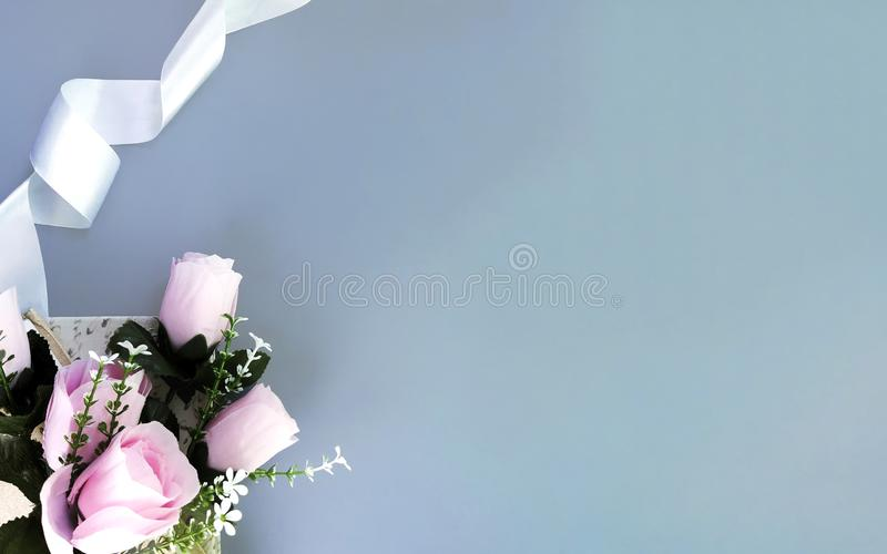 Silk ribbon, pink rose on grey background. Mothers day, Womens day, Valentines day, birthday or wedding concept. Silk ribbon, pink rose on grey background stock photography