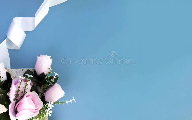 Silk ribbon, pink rose on blue background. Mothers day, Womens day, Valentines day, birthday or wedding concept. Silk ribbon, pink rose on blue background stock photo