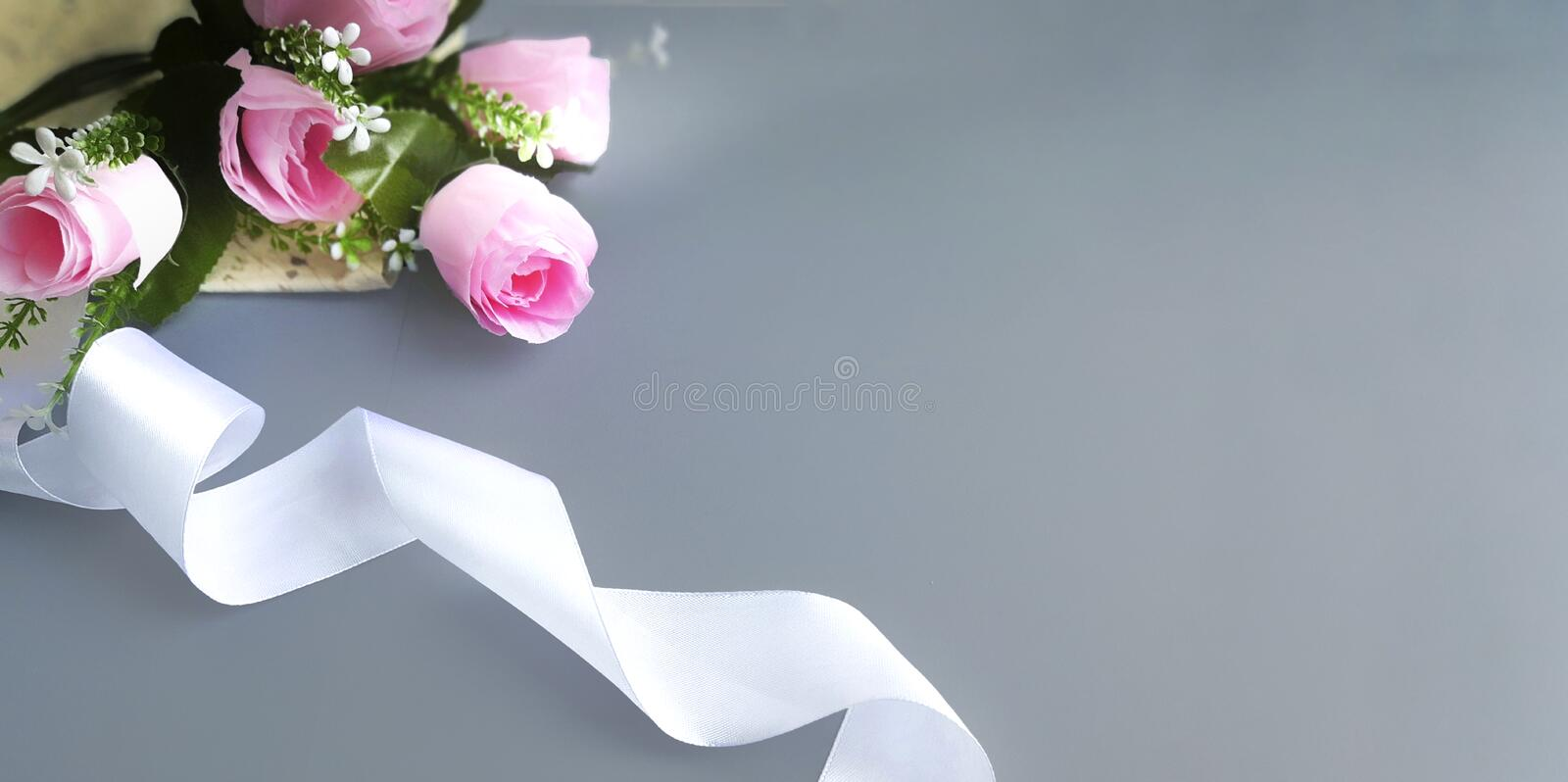 Silk ribbon, pink roses on grey background. Mothers day, Womens day, Valentines day, birthday or wedding concept. Silk ribbon, pink roses on grey background royalty free stock image