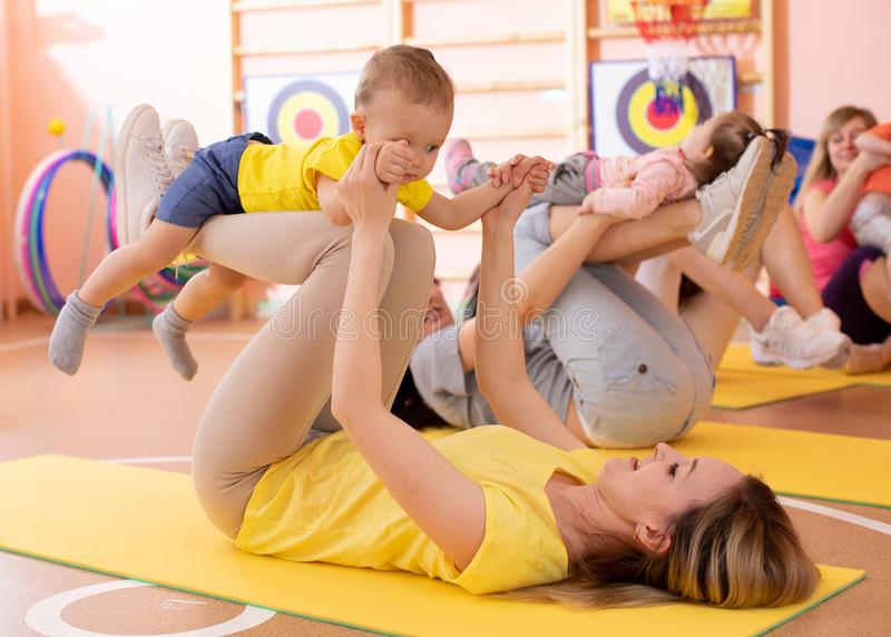 Mothers do fitness exercises together with their babies in daycare gym stock photography