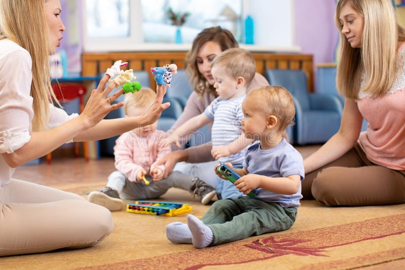 Mothers and their children together in club. Babies play with musical toys stock photos