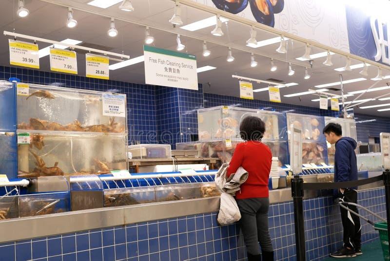 Motie van mensen die vissen kopen bij zeevruchtensectie binnen T&T-supermarkt stock foto's