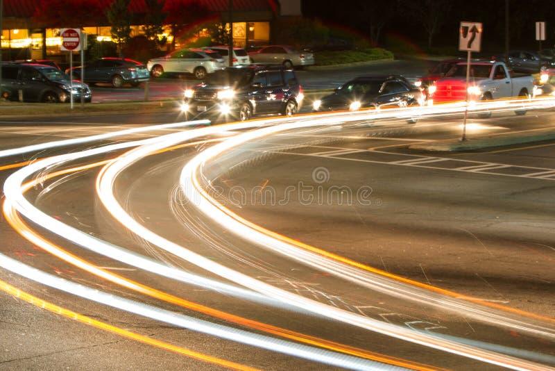 Motieonduidelijk beeld die van Autokoplampen bij Bezige Kruising draaien royalty-vrije stock foto's