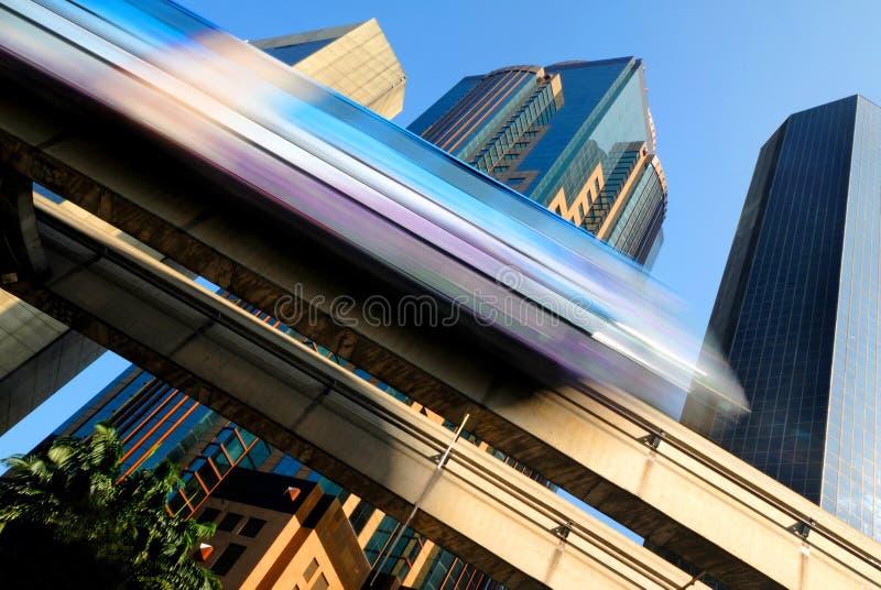 Motieonduidelijk beeld van een skytrain die door een modern bedrijfsdistrict verzenden royalty-vrije stock afbeeldingen