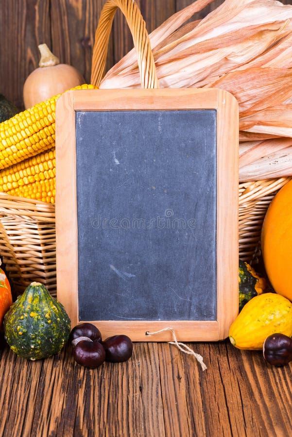 Motif de festival de récolte d'automne avec de divers potirons devant un panier avec des épis de maïs sur un fond en bois rustiqu images libres de droits